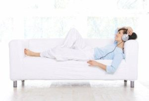 A lady on the sofa is enjoying a Hypnotherapy or Mindset-Booster session